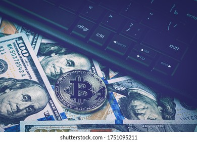 Dollar bills, black keyword and metal souvenir bitcoin. The concept of electronic money, online trading, mining and commerce. Cryptocurrency and cash.