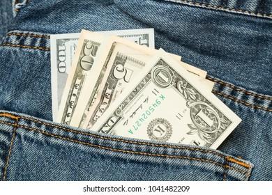 Dollar bills in a blue jeans pocket