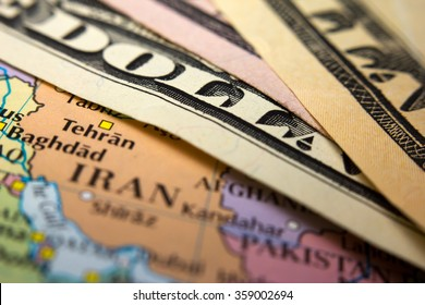 Dollar bills on top of a map of Iran