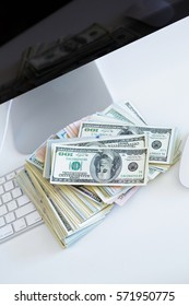 Dollar bills on the white computer keyboard - online payments concept