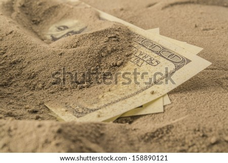 dollar bills partially buried in sand. Conceptual image depicting a safer alternative to investing. Macro with shallow dof.