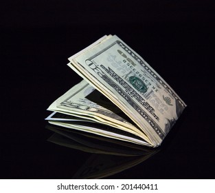 Dollar bills rolled up with clip on black background