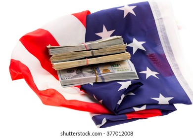 Dollar bills in stacks on a folded American flag isolated on white background