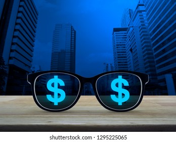 Dollar currency icon with eye glasses on wooden table over modern office city tower and skyscraper, Financial success concept