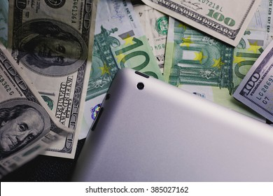 dollar and euro money, tablet, cell phone close up.