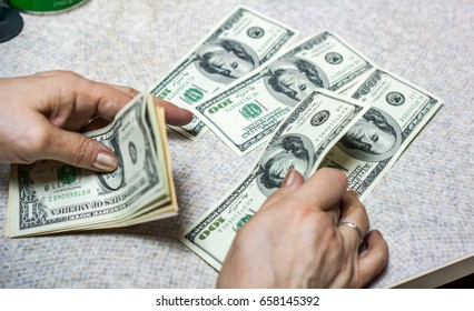 dollar in hands. women or man ounts dollar bills and get it into the light ivory grey table. Pile of new and old one hundred dollar bills.