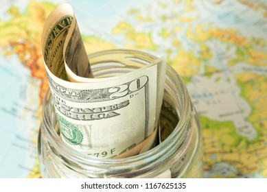 Dollar money bills in mason jar and an atlas