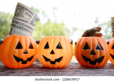 Dollar money and pile of gold coins inside pumpkin buckets on wood table in blur natural bright light