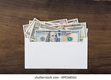 Dollar money in white envelop on wooden background. High resolution photo.
