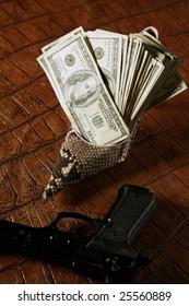 Dollar notes and gun, black pistol over crocodile black fake leather