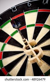 dollar pierced on same center of dartboard / bulls-eye