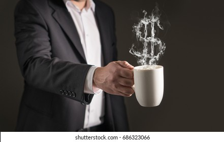 Dollar sign from coffee steam. Smoke forming a money symbol. Business man in a suit holding a hot beverage in a mug and tea cup.