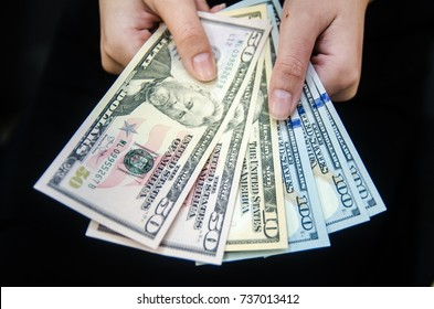 Dollar (USD), United States (USA) money, Women holding  money currency of United States on black background. business and finance concept.