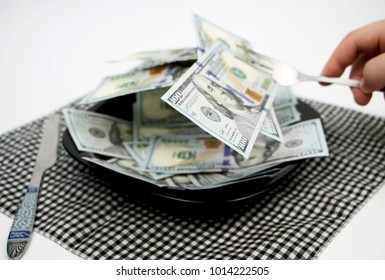 Dollars, banknotes one hundred dollars on a plate. The concept of greed and wealth