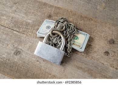 Dollars and a big silver lock on wooden table. copy space.