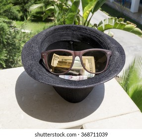 dollars in a black hat with sunglasses on a sunny day