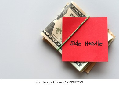 Dollars cash money and paper note with text written SIDE HUSTLE on background - concept of financial planning - make more extra money from parttime side hustle or second job