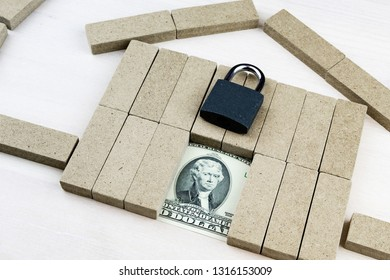 dollars in the door of a toy house and padlock on the house assembled from bars