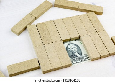 dollars in the doors of a toy house assembled on a wooden surface