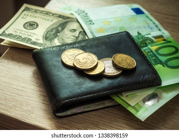 Dollars and euro banknotes and coins in a wallet. Personal finance concept