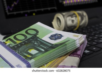 A lot of dollars and euros on the table near the computer