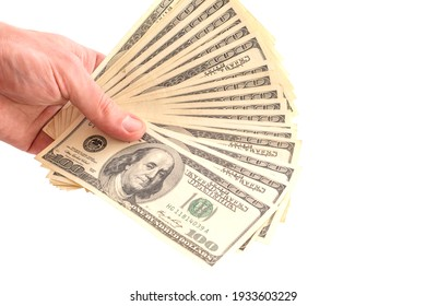 Dollars fan in a female hand isolated on white background. Clipping Path. 100