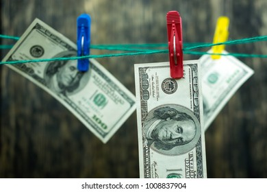 Dollars hang on a rope on clothespins.