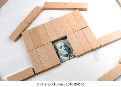 dollars and the house, the symbol of the house on a wooden table collected from toy building materials