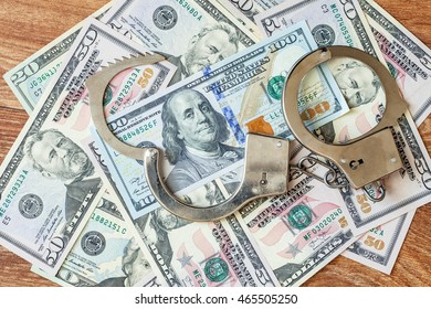 Dollars of hundred and fifty dollars lie on a floor and from above handcuffs for detention of the corrupt official on polichny are put.