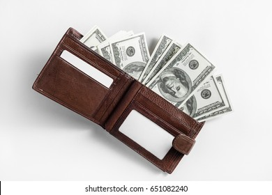 Dollars in a leather wallet on paper background. One hundred dollar bills. Top view.