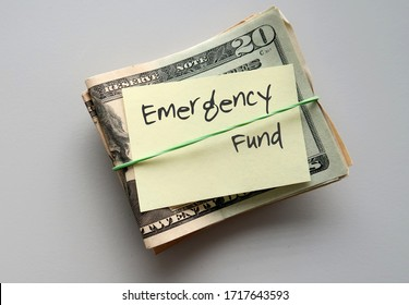 Dollars Money and paper note with text written on EMERGENCY FUND on background with copy space - concept of financial planning  saving money for purpose of rainyday crisis tough time