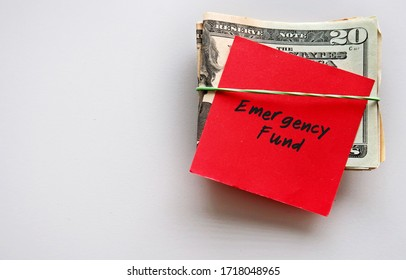Dollars Money and red paper note with text written on EMERGENCY FUND on background with copy space - concept of financial planning  saving money for purpose of rainyday crisis tough time