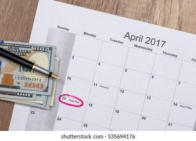 Dollars on the calendar - april 2017 with pen on desk.
