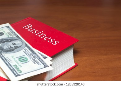 a lot of dollars on a red book. on the book the inscription business. The concept of business success, business acumen, success, wealth. copy space.