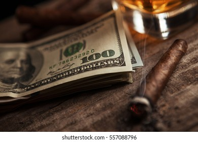 Dollars on wooden table with glass with brandy and smoking cigarette