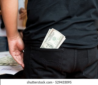 Dollars in the pocket of jeans Bundle of dollars Money in the pocket of trousers,A person pulling a dollar bill out of a denim blue jean back pocket
