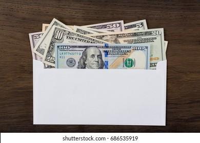 Dollars in white envelop on wooden background. High resolution photo.