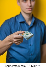 Dollars. A young man close-up in a blue shirt on a yellow background, gives or takes money. Holds money in hands. . Photos