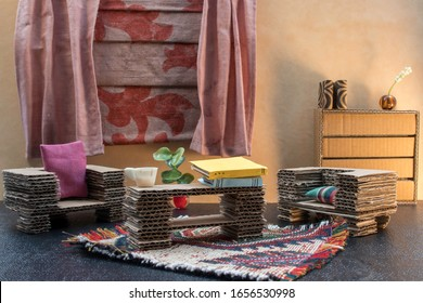 Dollhouse living room with cardboard furniture.