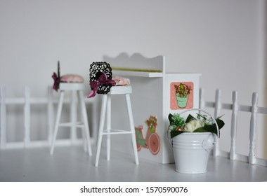 Dollhouse terrace , with bar and white chairs. Decoration with flowers and lavish colors