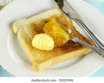 Dollops of orange marmalade and butter on a slice of toast.