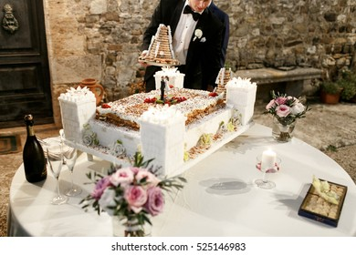 Dolls of kissing newlyweds stand on the square wedding cake
