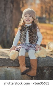 Dolly pin-up toothsome young brunette girl wearing fashion stylish gray jacket jerkin and warm hat with awesome boots clothes posing autumn spring park weekend happyly smiling sitting pathway track