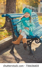 Dolly pin-up toothsome young girl wearing turquoise light blue jacket and warm hat fashion stylish clothes posing in autumn spring park weekend happyly smiling sitting on pathway track