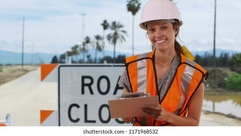 Dolly shot of Female worker in safety vest standing in front of road closed sign