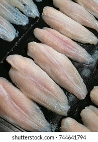 Dolly white meat fishes arranged on black plate.