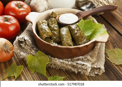 Dolma from grape leaves and minced on the wooden table