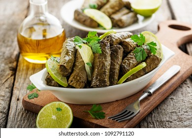 Dolma, stuffed grape leaves with rice and meat on wooden  background .