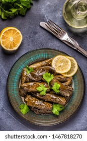 Dolma, stuffed grape leaves with rice and meat on dark background, top view.