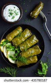 Dolma, stuffed grape leaves with rice and meat. Top view. Black background.
